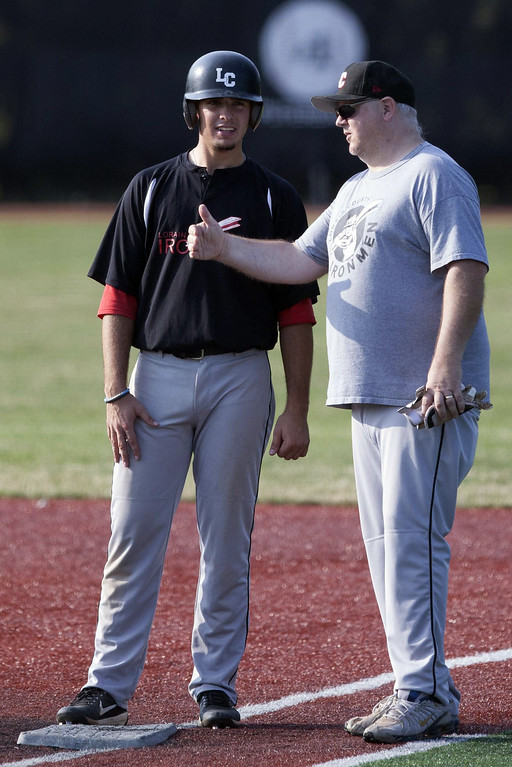 . Jen Forbus - The Morning Journal Ironman baserunner Kenny Pierson gets some pointers from his first base coach.
