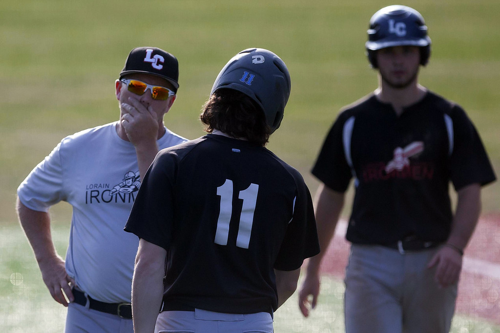 . Jen Forbus - The Morning Journal Ironman Jacob Lozinski consults with his third base coach during Lorain County\'s contest against the Lake Erie Warhawks.
