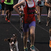 Michael Johnson  - The News-Herald<br /> Alison Martin runs with her dog during the Friday Night Lights 5K at Mentor High School on July 15.