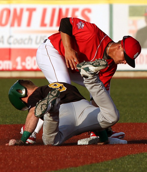 Eric Grabe tries to pick off Mitch Elliot of the Cornbelters at second base. Randy Meyers -- The Morning Journal