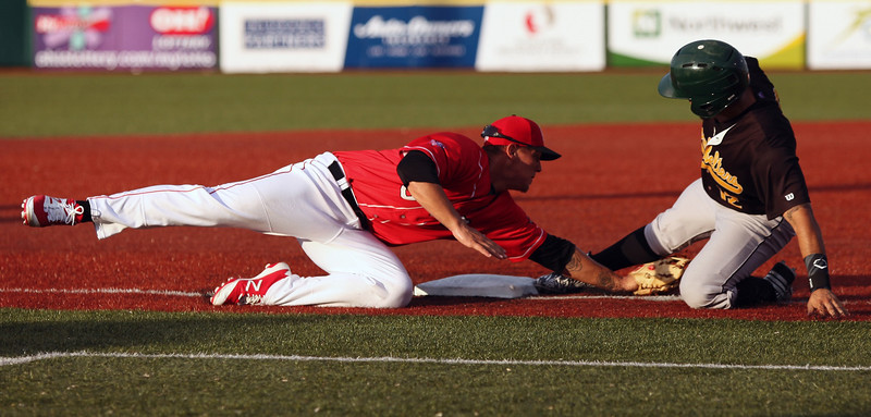 Santiago Chirino of the Cornbelters is called out at third as the Crushers's Eric Grabe makes the tag. Randy Meyers -- The Morning Journal