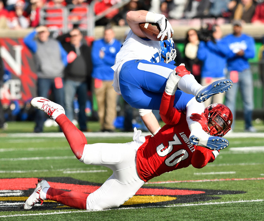 . Louisville\'s safety Khane Pass (30) wraps up Kentucky\'s tight end C.J. Conrad (87) during the second half of an NCAA college football game, Saturday, Nov. 26, 2016, in Louisville, Ky. Kentucky won 41-38. (AP Photo/Timothy D. Easley)
