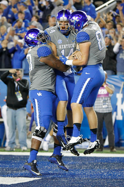 . Kentucky quarterback Patrick Towles, center, celebrates his touchdown with teammates Kyle Meadows, left, and C.J. Conrad during the first half of an NCAA college football game against Missouri, Saturday, Sept. 26, 2015, in Lexington, Ky. (AP Photo/David Stephenson)