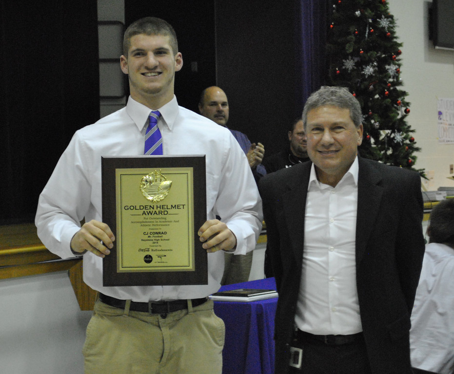 . Jon Behm - JBehm@MorningJournal.com<br> Keystone\'s C.J. Conrad, left, was presented the Golden Helmet award by Coca-Cola representative Gregory Finton at the Wildcats\' banquet on Dec. 4. The award is given to the top senior football player in Lorain County.