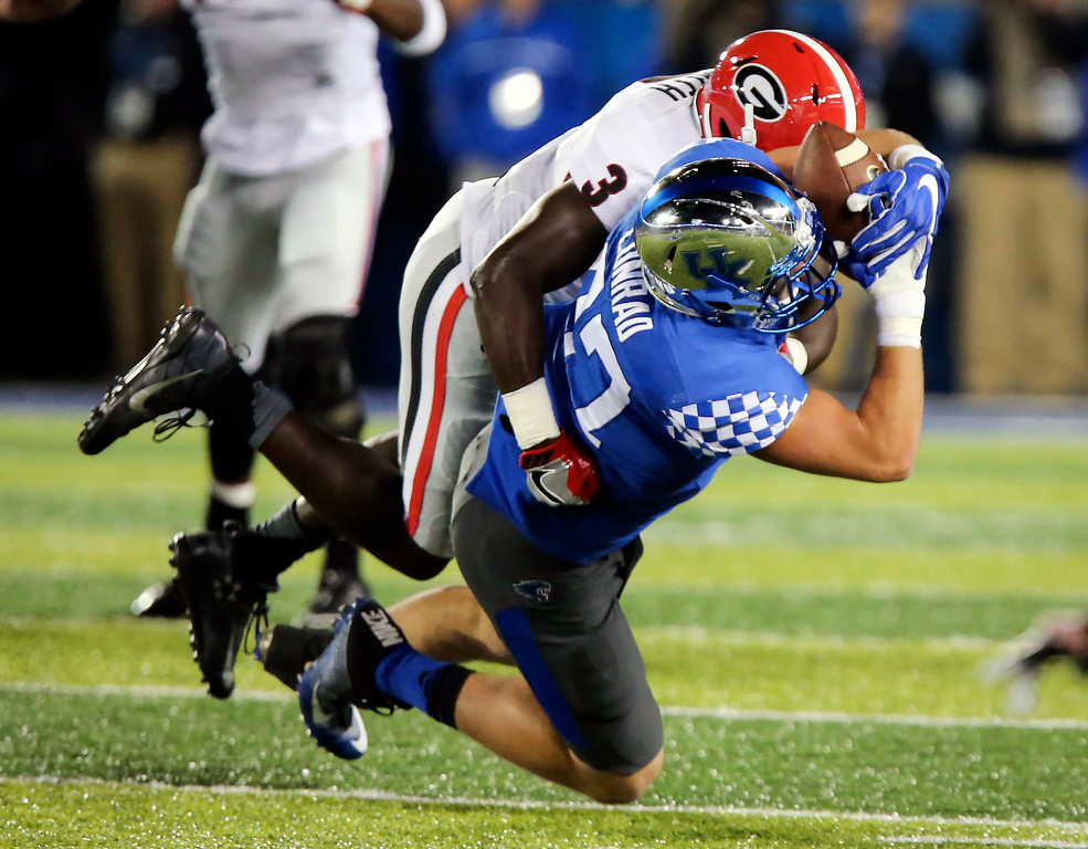 . Kentucky tight end C.J. Conrad, bottom, cannot control a pass as he is hit by Georgia linebacker Roquan Smith in the first half of an NCAA college football game Saturday, Nov. 5, 2016, in Lexington, Ky. (AP Photo/David Stephenson)