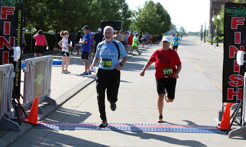 Randy Meyers - The Morning Journal<br> Runners John Paul, left, and Teresa Starkey cross the finish line at the eighth annual Journal Jog on July 30.