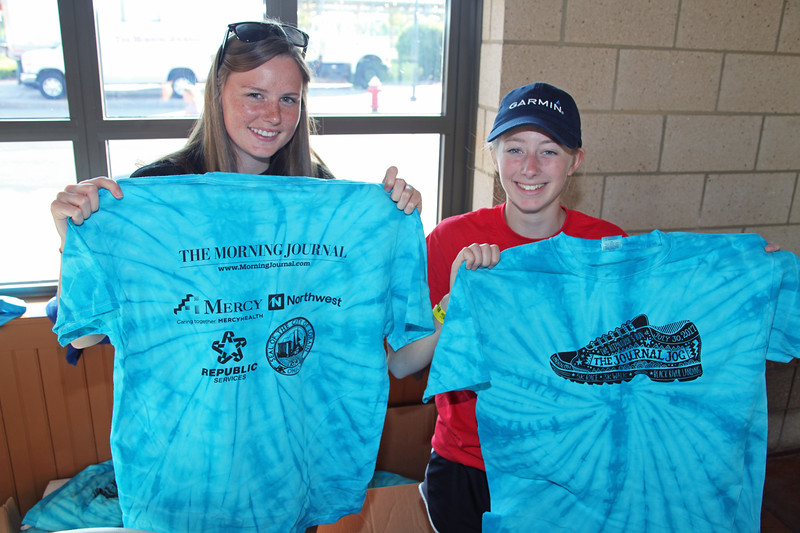 Randy Meyers - The Morning Journal<br> Journal Jog volunteers Elizebeth Gilreath and Carolyn Skledar pass out t-shirts to the race participants on July 30.