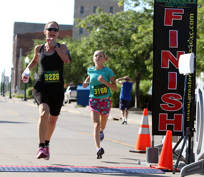 Randy Meyers - The Morning Journal<br /> Pamela Bahm, left, and Savannah Reed cross the finish line at the eighth annual Journal Jog on July 30. Bahm was the women's 40-44 age group winner, while Reed won the 12-and-under group.