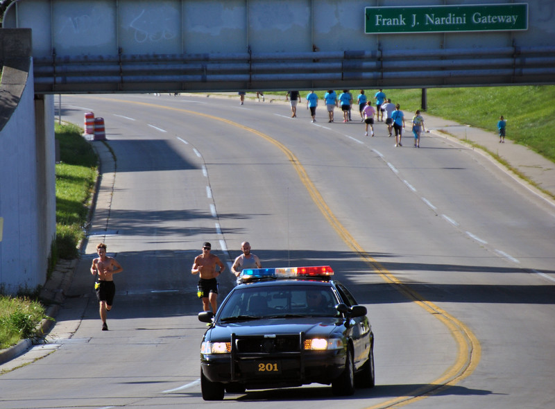 Jon Behm - The Morning Journal<br> The top-three runners make thier way back up Broadway and under the Frank J. Nardini Gateway bridge as 3K walkers work down Broadway during the eighth annual Journal Jog on July 30.