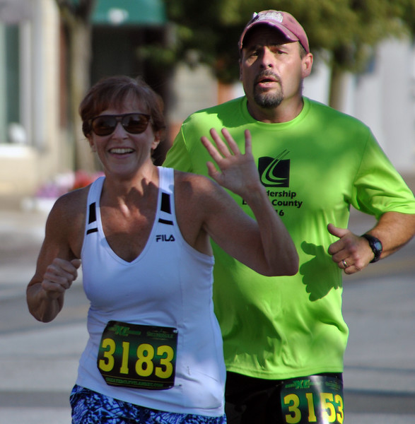 Jon Behm - The Morning Journal<br> A quick wave to the camera did not slow down Mary Van Almen, who placed second in the women's division during the eighth annual Journal Jog on July 30 with a time of 22:26.5. She is followed closely by James Martin, of Wellington.