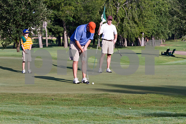Photo by Shannon Wilson / Tyler Morning Telegraph  Drew Gillen puts while his son Will Gillen (8) and Mike Clendenin looks on during the 2013 Men's Club Championship at the Hollytree golf course on Saturday morning.