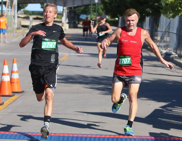 Amanda K. Rundle - The Morning Journal<br /> Victor Yavornitzky, left, battles with George Kubelik for the edge as the duo crosses the finish line at the 7th Annual Journal Jog on Aug. 7.