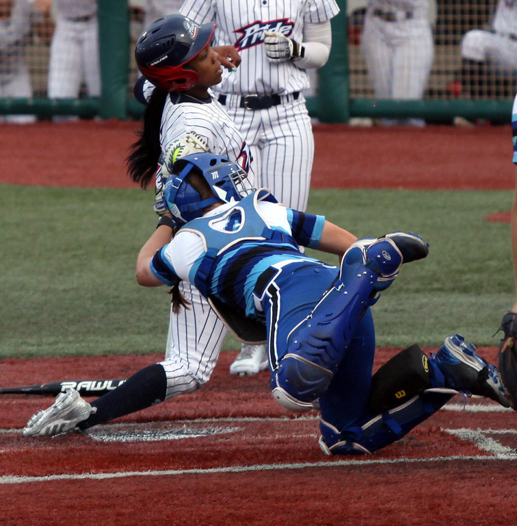 . Randy Meyers - The Morning Journal Bianca Bell of the USSSA Pride  slides into home and beats the tag by Cleveland Comets catcher Randi Rupp  on Wednesday