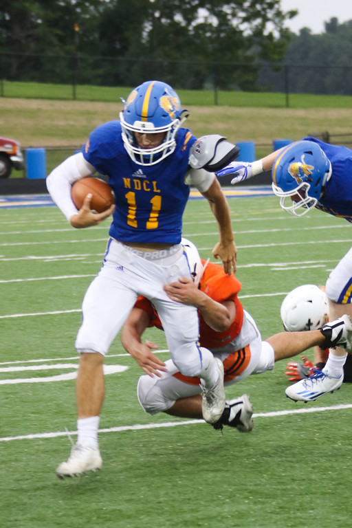 . NDCL quarterback Nick Gatozzi (11) tries to break free from an Eastlake defensive player.