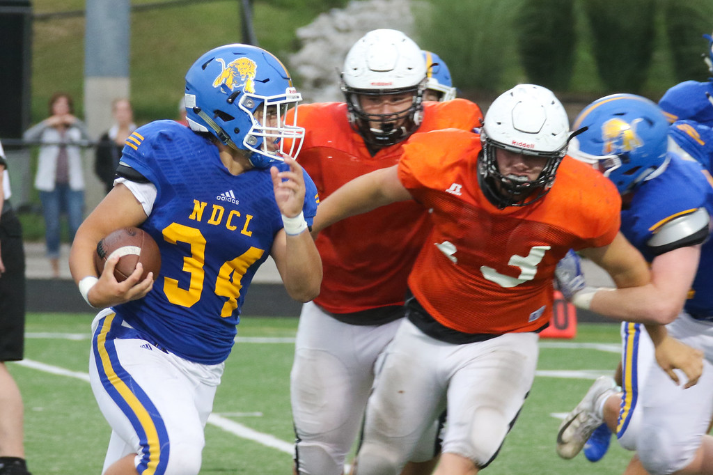 . NDCL runningback Zach Urda (24) carries the ball pursued by Eastlake\'s Sean Turschon (73).
