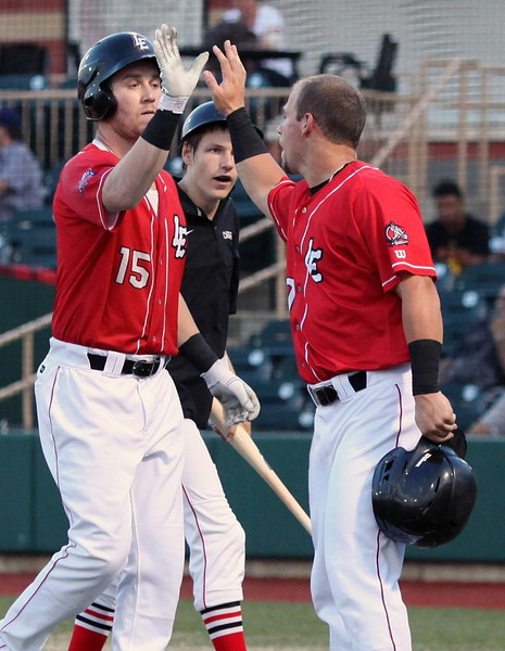 The Crushers' Sean Hurley, left, is congratulated by teammate Robb Paller after hitting a three-run homer. Randy Meyers -- The Morning Journal