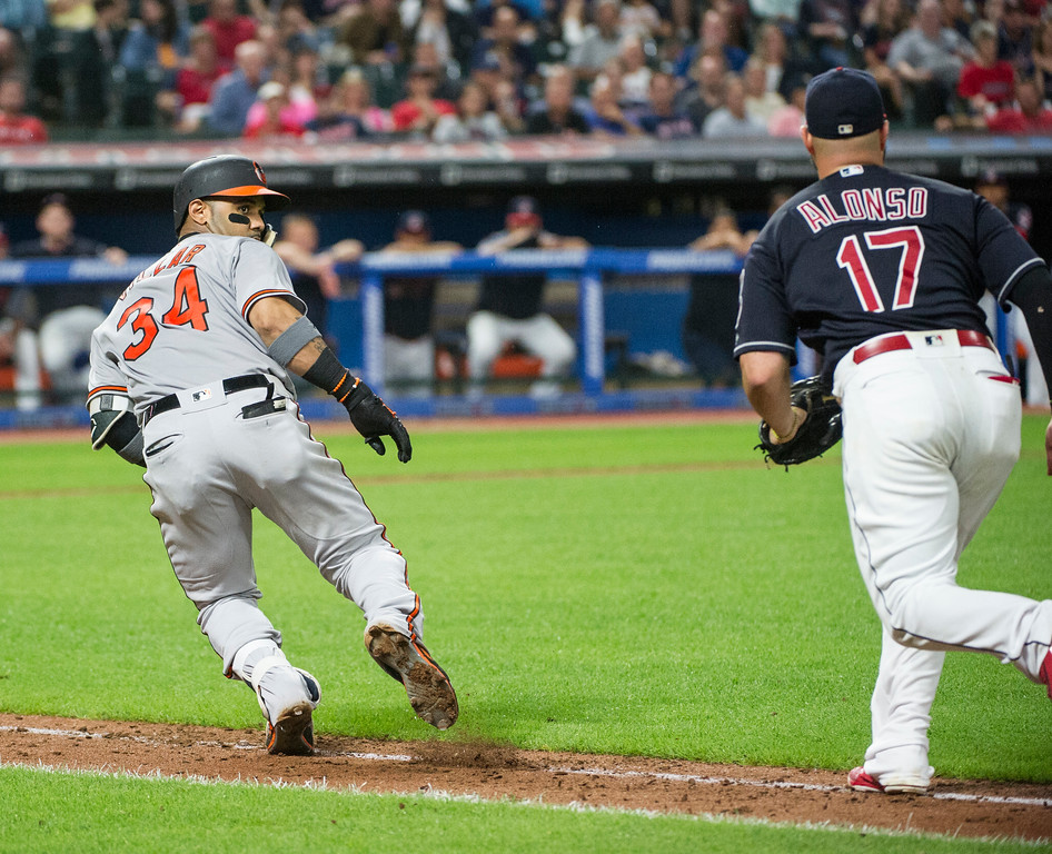 . Baltimore Orioles\' Jonathan Villar runs back towards home plate as Cleveland Indians\' Yonder Alonso chases him during the eighth inning a baseball game in Cleveland, Friday, Aug. 17, 2018. (AP Photo/Phil Long)