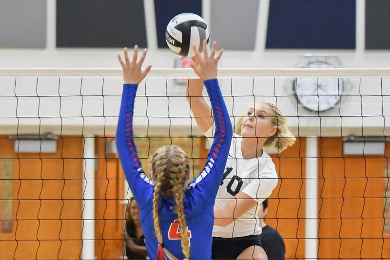 Lorain's Raegan Osko spikes the ball through the hands of Open Door's Zelie Kessler. Eric Bonzar -- The Morning Journal