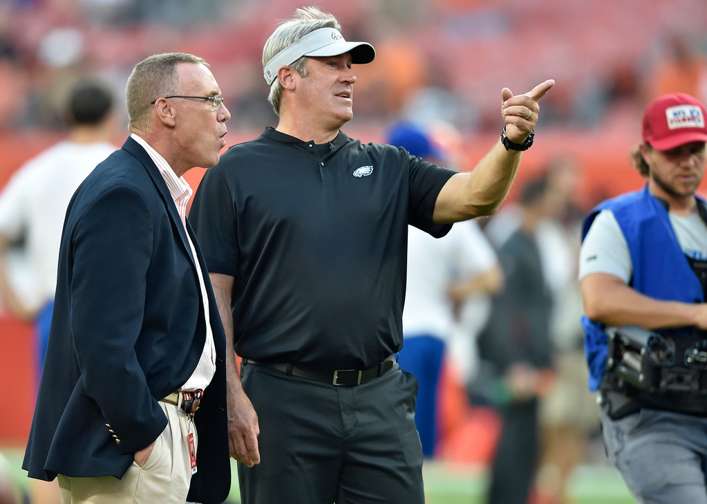 . Cleveland Browns general manager John Dorsey, left, talks with Philadelphia Eagles head coach Doug Pederson before an NFL football game between the Cleveland Browns and the Eagles, Thursday, Aug. 23, 2018, in Cleveland. (AP Photo/David Richard)
