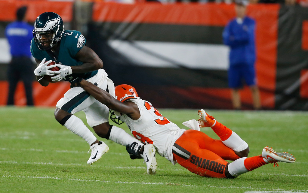 . Cleveland Browns defensive back T.J. Carrie (38) tackles Philadelphia Eagles wide receiver DeAndre Carter (2) on a punt return during the first half of an NFL preseason football game, Thursday, Aug. 23, 2018, in Cleveland. (AP Photo/Ron Schwane)