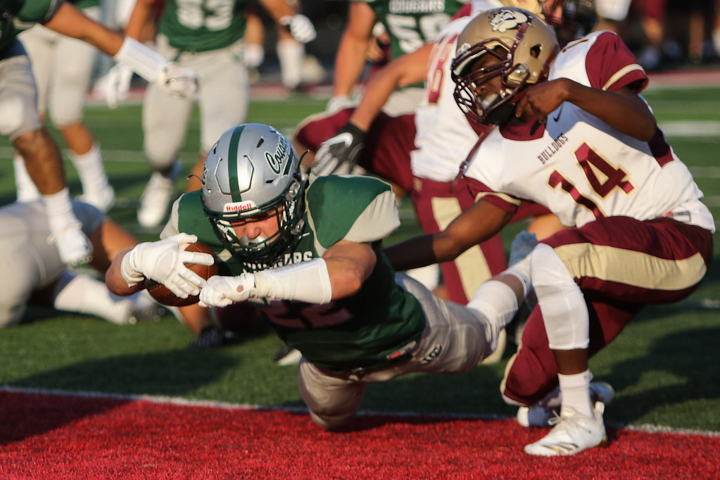 . 2018 - Football - Stow at Lake Catholic.  Lake Catholic defeated Stow 31-7.  Lake Catholic runningback Nate Rieple (22) dives across the goal line past Stow defender Demarrion Garske (14) for the first score of the game.
