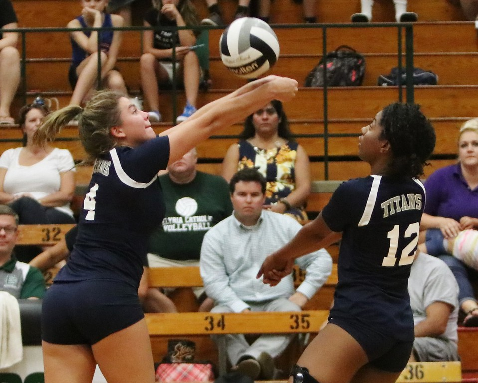 . Lorain\'s Lauren Evans (4) and Lindsey Williams (12) rush to get the the ball over the net . Amanda K. Rundle -- The Morning Journal