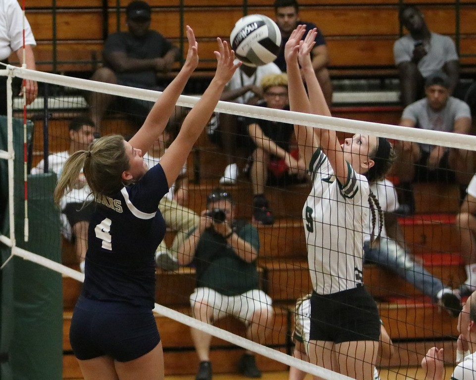 . Lorain\'s Lauren Evans (4) and Elyria Catholic\'s Haley Raible (9) go for the ball at the net. Amanda K. Rundle -- The Morning Journal