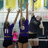Tory Small of Amherst tips the ball over Gillian Romanchok and Katie Sopko of Avon for a point. Randy Meyers -- The Morning Journal