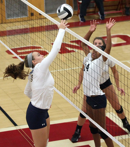 Samanatha Howst of North Ridgeville taps the ball over Lorain's Seven Townsel at the net. Randy Meyers -- The Morning Journal