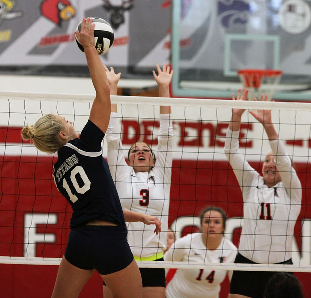 Raegan Osko of Lorain spikes the ball over Victoria Grasso and Bianca Inman of Firelands for a point. Randy Meyers -- The Morning Journal