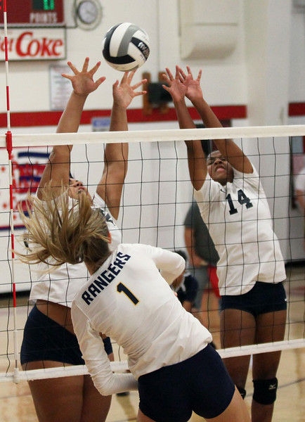 Maia Wasuk of North Ridgeville hits the ball over Lorain's Paige Murphy and Seven Townsel. Randy Meyers -- The Morning Journal