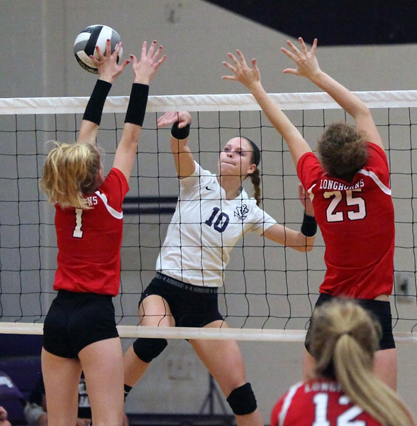 Vermilion's Caitlyn Schnur spikes the ball off the hands of Lutheran West's Sydney Lapointe for a point. Randy Meyers -- The Morning Journal