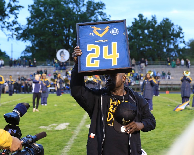 Tim Phillis - The News-Herald<br /> Andre Jackson's father Andre Littlejohn holds up his son's jersey..