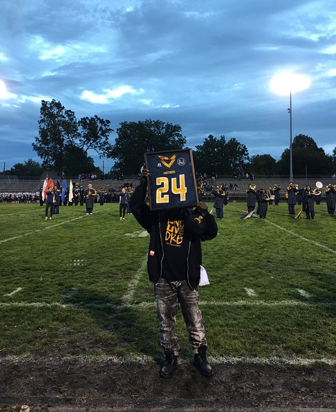 Tim Phillis - The News-Herald <br /> Andre Jackson's father holds up a jersey honoring his late son on Sept. 30.