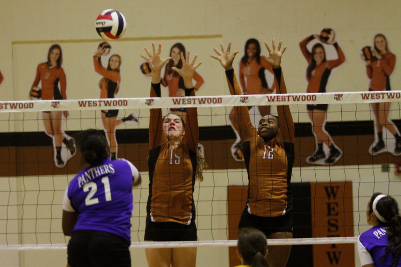 Westwood's Sarah Afflerbaugh, 15, and Tian Houston, 12, go up for a block against Pflugerville on Tuesday at Westwood High School.