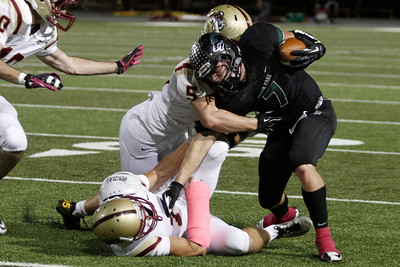 Cedar Park's Ethan Fry is taken down by Rouse players Friday at Gupton stadium.