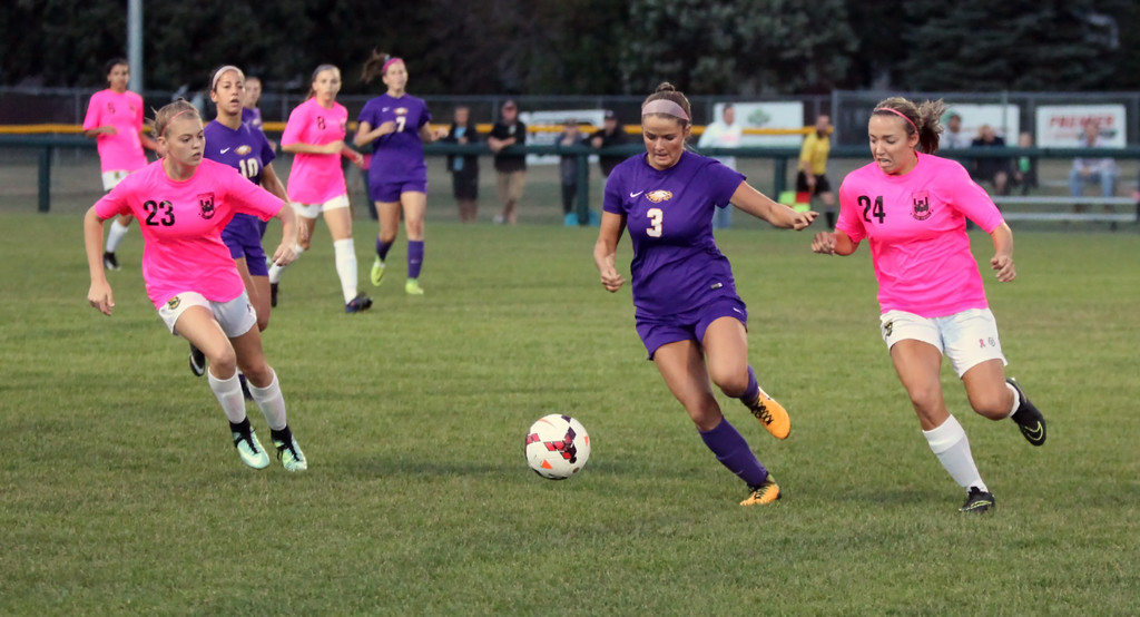 . Avon\'s Emily Dahl moves the ball in between Laruen Kachure and Sydney Schaefer of Amherst during the first half. Randy Meyers -- The Morning Journal