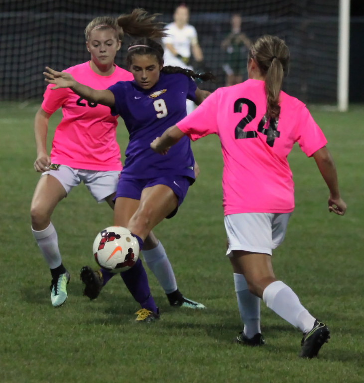 . Avon\'s Taylor Golas moves the ball in between Sydney Schaefer and Lauren Kachire of Amherst during the first half. Randy Meyers -- The Morning Journal