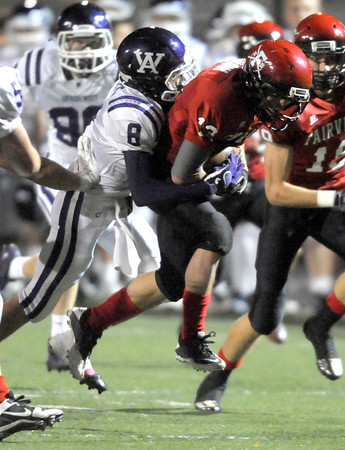 Fairview's Ben Bulow (right) is dragged down by Arvada West's Tyler Follett (left) after Bulow intercepted a pass during their football game at Recht Field in Boulder, Colorado October 6, 2011.  CAMERA/Mark Leffingwell