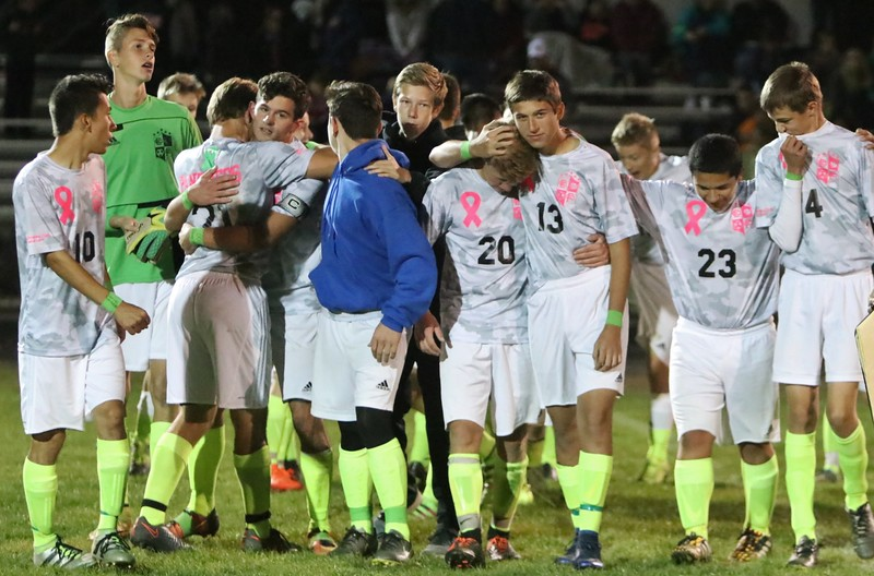 The Elyria Catholic coys soccer team comes off the field after their win over Hearts for Jesus Christ to honor Jakob Hwang. Amanda K. Rundle -- The Morning Journal