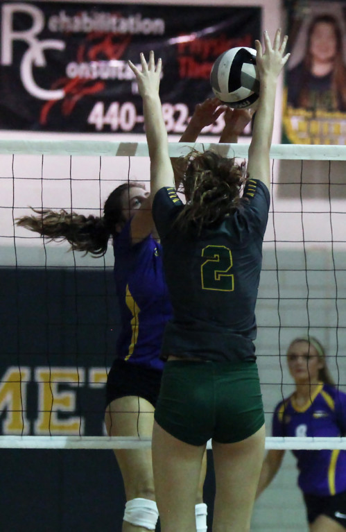 . Avon\'s Isabella LaBianca has her tip blocked by Sarah Farley of Amherst during the second set. Randy Meyers -- The Morning Journal