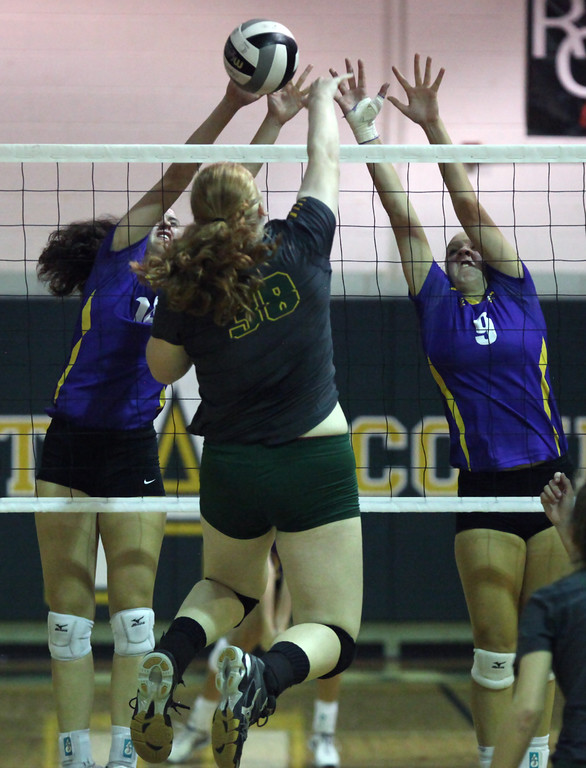 . Tory Small of Amherst has her shot blocked by Katie Koziarz and Gillian Romanchok of Avon during the second set. Randy Meyers -- The Morning Journal