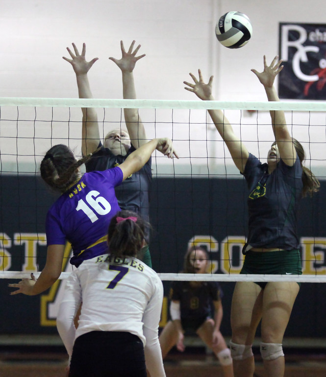 . Avon\'s Isabella LaBianca spikes the ball over Payton Jackson and Tory Small of Amherst during the first set. Randy Meyers -- The Morning Journal