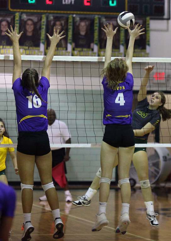 . Payton Jackson of Amherst spikes the ball over Sydney Stone of Avon during the first set. Randy Meyers -- The Morning Journal