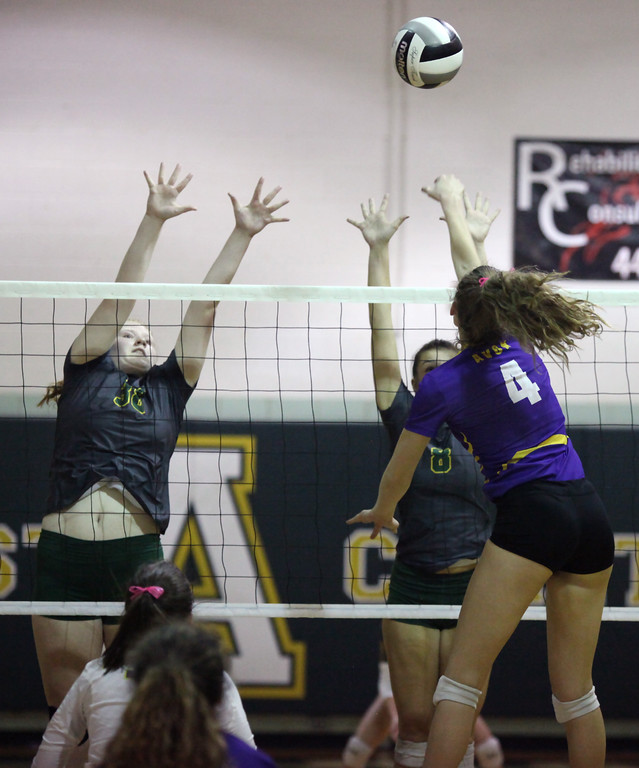 . Avon\'s Sydney Stone taps the ball over Sarah Wiegand and Tory Small of Amherst during the second set. Randy Meyers -- The Morning Journal