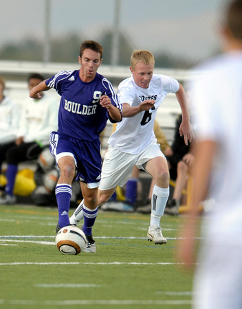 Boulder's Ben Kates (left) takes the ball up field while being pressured by Monarch's Jamie Falloon (right) during their soccer game at Monarch High School in Louisville, Colorado October 11, 2011.  CAMERA/Mark Leffingwell