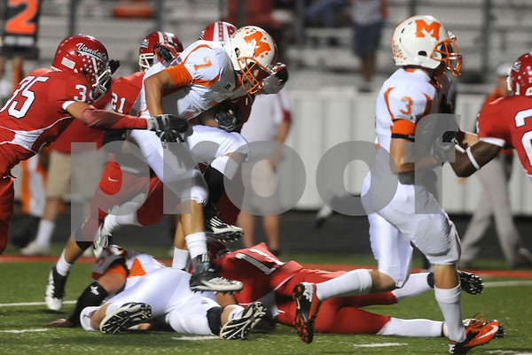 photo by Sarah A. Miller/Tyler Morning Telegraph  Mineola's Rhett Self jumps over several players as he carries the ball in the first half of their game at Van Friday night.