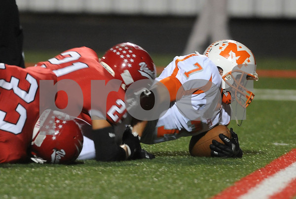 photo by Sarah A. Miller/Tyler Morning Telegraph  Mineola's Rhett Self jumps is tackled by Van's (21) Ben Buchanan and (33) Bryce Krumvieda in the first half of their game at Van Friday night.
