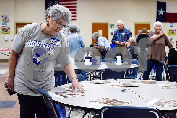 Janice Williams Bates looks at old photos at a reunion during a high school football game at Hawkins High School in Hawkins, Texas, on Friday, Oct. 13, 2017. The 1967 regional championship football team reunited for Hawkins' homecoming game. (Chelsea Purgahn/Tyler Morning Telegraph)