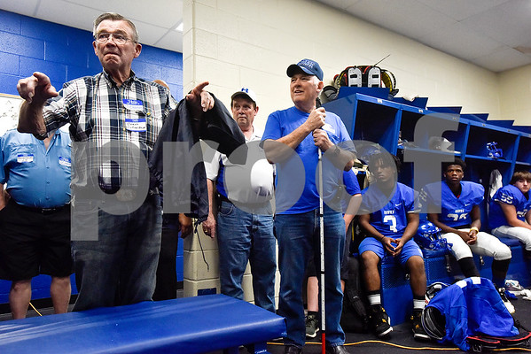 Winfred Shipp, coach of the 1967 regional championship football team, left, speaks to his team and the current Hawkins varsity football team during a high school football game at Hawkins High School in Hawkins, Texas, on Friday, Oct. 13, 2017. The 1967 regional championship football team reunited for Hawkins' homecoming game. (Chelsea Purgahn/Tyler Morning Telegraph)